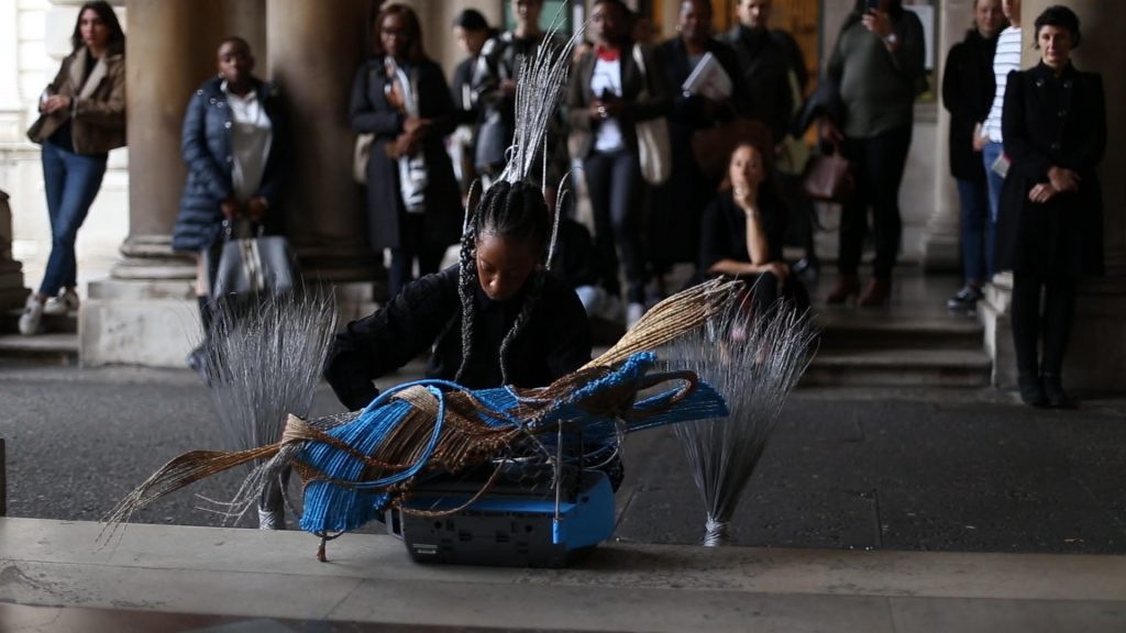 Adejoke Tugbiyele, Shifting The Waves: The mask, The Boat, The Broom, The Box, 2017. Image from the performance at 1:54 Contemporary Art Fair, London. Image copyright Ade Odetola, courtesy the artist.