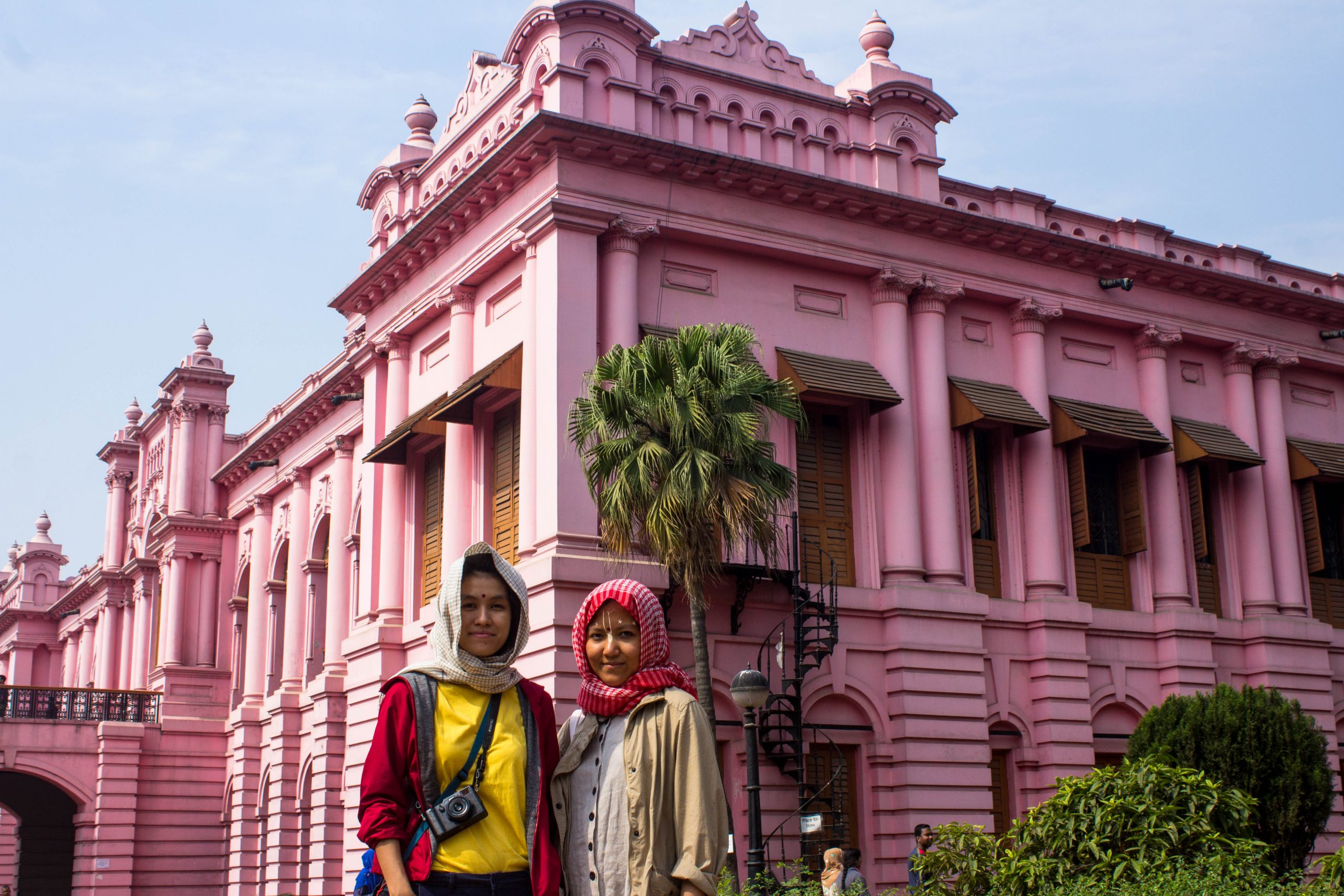Photo: Khin et Rita. Image of two ladies in front of a pink building