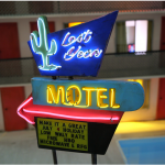 """""""Lost Year Motel"""" (2020) by 2020 Foundwork Artist Prize Honoree Tracey Snelling. Wood, plaster, paint, metal, lights, fabric, lcd screens, media players, electroluminescent wire, water, speakers, transformer. 24 x 50 x 24 in."""